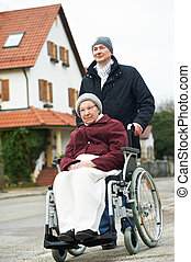 old senior woman in wheelchair with careful son