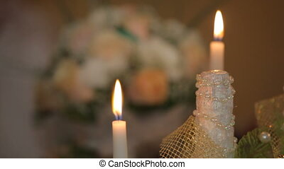 Burning candles and bouquet of roses. Close up.
