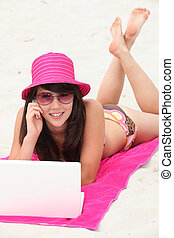 Young woman in a bright pink straw hat using her laptop computer on the beach