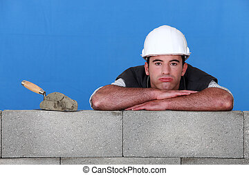 bricklayer with trowel head resting on arms