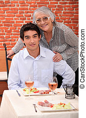 a young man and an old woman at the restaurant posing for...