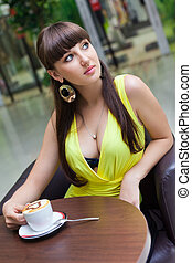 Beautiful girl having coffee at caf - The beautiful young...