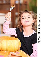young girl carving a pumpkin