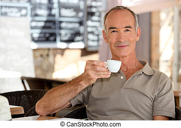 Elderly man having an espresso on a terrace