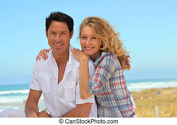 Happy couple relaxing at the beach
