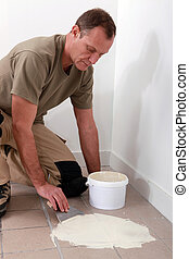 Man spreading adhesive over old floor tiles