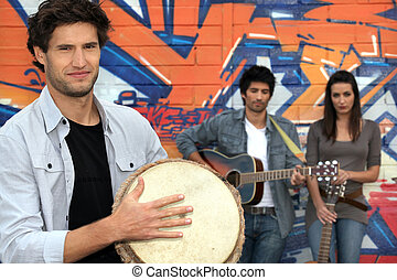three musicians in front of a tagged wall