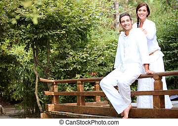 a couple on a wooden bridge in a park
