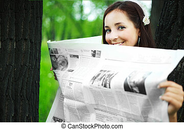 girl reading a newspaper - pretty young brunette woman...