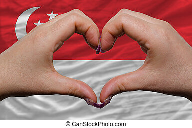 Gesture made by hands showing symbol of heart and love over...