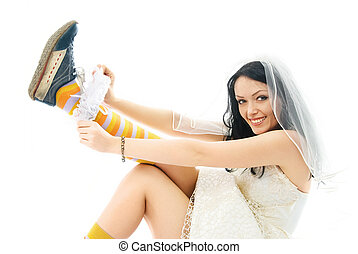 bride wearing sporting shoes puts on a garter - funny young...