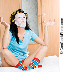 young woman wearing hair curlers and a mask sitting on the...