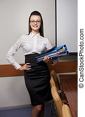 Portrait of relaxed young business woman smiling at office with documents in glasses
