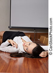 Beautiful sexy  business woman lying on the desk in the office