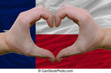 Gesture made by hands showing symbol of heart and love over us state flag of texas
