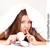 woman eating cookies - beautiful young woman hiding under...