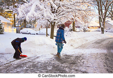 Snow Removal - Two people shoveling snow on after a heavy...