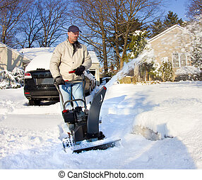 Snow Removal - Man with snow blower removing snow