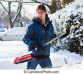 Snow Removal - Young man removing snow