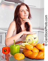 woman cooking - happy beautiful young woman cooking in the...