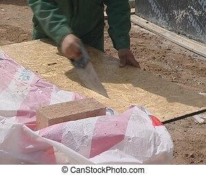 hand cut board handsaw - Worker cutting wood sawdust board...