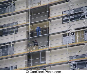 Builder renovation - Builders working on scaffolding. Old...