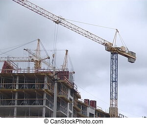 Crane builder construct - Cranes and people building the...