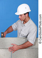 Bricklayer tapping down a block wall