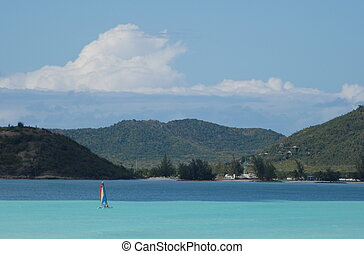 Turquoise sea in Antigua - Yacht with rainbow sail in...