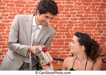 Man offering woman gift in restaurant