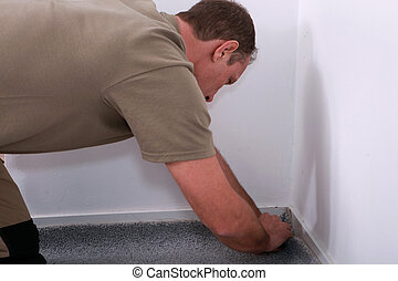 Carpet fitter tucker the edges into the corner of a wall