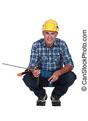 Man crouching with drill