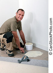 Smiling carpet fitter spreading adhesive on an old tiled...