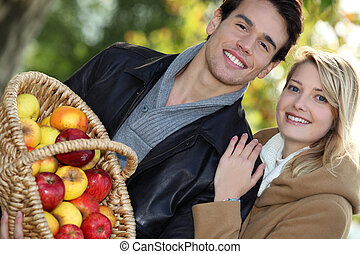 young couple all smiles with basket full of apples