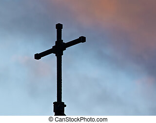 Holy cross on top of a dutch chapel under a dramatic sky