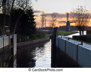 Dutch lock chamber with vintage windmill backdrop during...