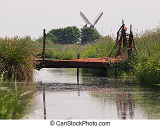 Rusty bridge in rural landscape with vintage wind mill in...