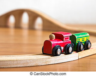Red and green wooden toy train on railroad with bridge in...