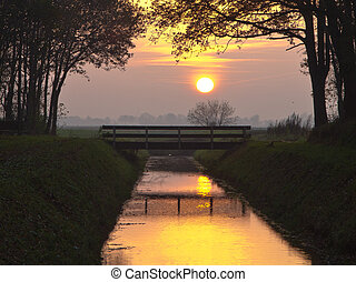Yellow sunset over bridge and canal in a park