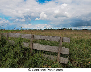 Fence in nature reserve with clouded summer sky