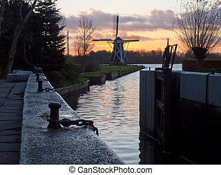 Vintage windmill backdrop during sunset with lock chamber...