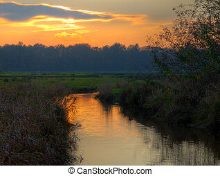 Sunset over small rural river in nature reserve