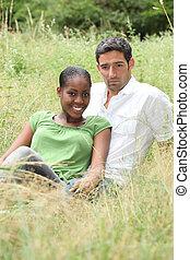 Couple sat in a field