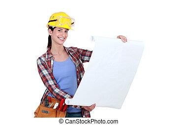 Tradeswoman examining a blueprint