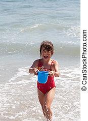 pequeno, menina, tocando, balde, praia
