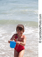 Little Girl Playing with a Bucket on the Beach - Very...
