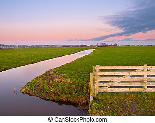 Gate to a meadow in dutch rural landscape during sunset