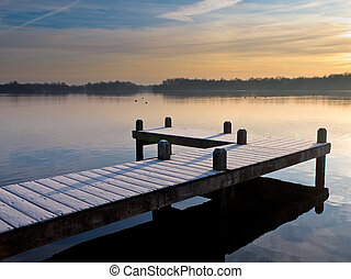 Pier at lake during wintertime sunrise