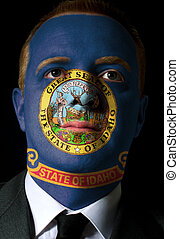 High key portrait of a serious businessman or politician whose face is painted in american state of idaho flag