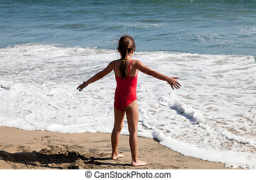 Little Girl Waiting for the Ocean Wave - Little girl playing...